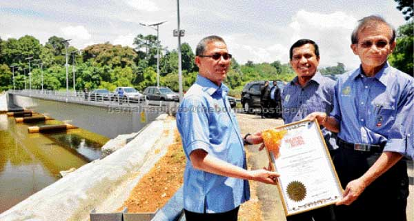 Fadillah (left) presents 'The Malaysia Book of Records' certificate to  Perak PWD director Datuk Dr Safry Kamal Ahmad after visiting the Batu 6 Bridge in Gerik. — Bernama photo