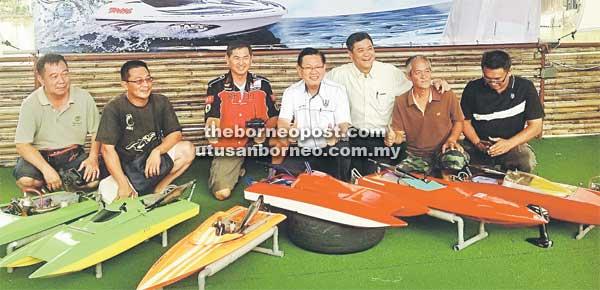 BAKAL BERSAING: Lee (tengah) Edward (tiga kanan) dan ahli jawatankuasa penganjur bersama sebahagian bot mengambil bahagian pada Pertandingan Bot Kawalan Jauh 2015 pada 25 dan 26 Julai di Tasik Jumbo, Desa Senadin.