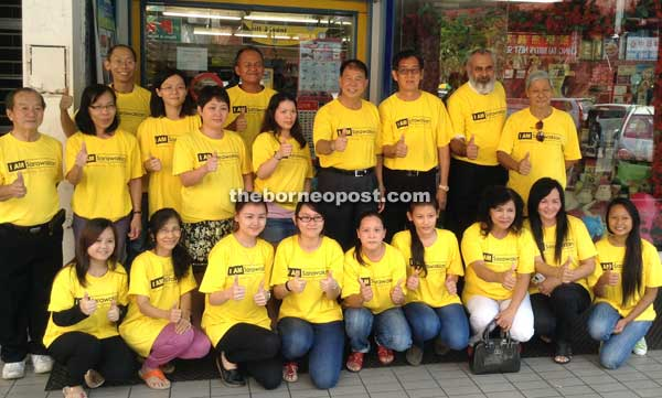 Ting (standing fourth right) with SUPP members and staff of Toys World wearing their `I AM Sarawakian' t-shirts during a promotion drive last Thursday.