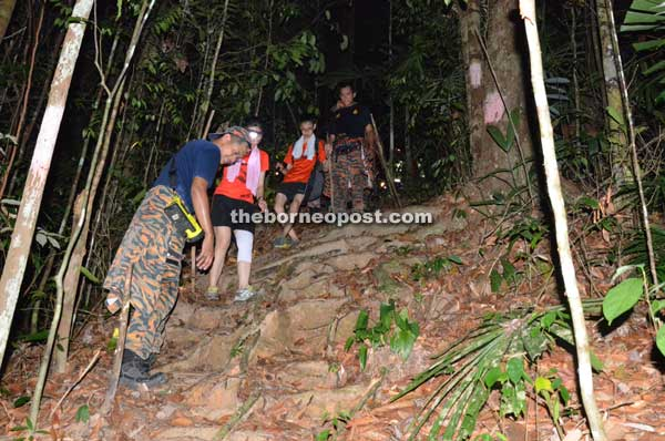 Homeward bound are personnel from Miri fire station seen hiking down the trail with the two rescued hikers.