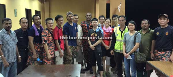 The rescued hikers (standing sixth and seventh from right) posing for a group photo with their rescuers after they arrived at the base station on Friday night.