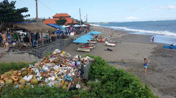 A mound of trash generated by nearby stalls and businesses is an eyesore on a popular surfing beach frequented by tourists and locals in Bali.