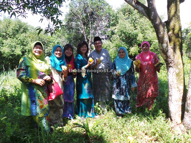 Awang Tengah (third right) and his wife Datuk Dayang Morliah Awang Daud (fourth left) are delighted to return to their roots as they can enjoy the fruits in their family orchard at Kampung Dato.