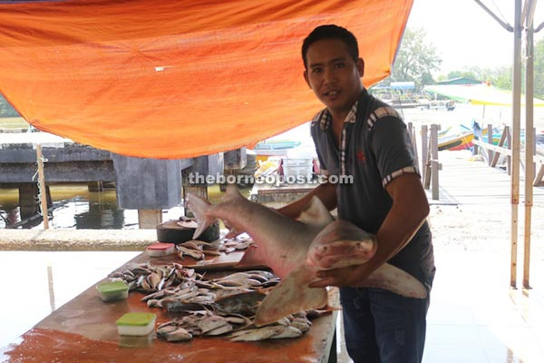 Fishmonger Mohammad Zakaria showing off his 17.5 kg catch of the day.