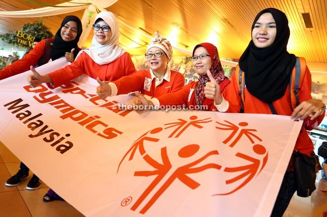 ENCOURAGEMENT: Minister of Welfare, Women and Family Development Datuk Fatimah Abdullah (second left), Kuching Special Olympics Chapter chairman Datin Dayang Mariani Abang Zain (third left) and coach Ruhana Bujang (second right) flashing the thumbs-up to special athletes from Sarawak participating in the World Summer Games in Los Angeles from July 25 to Aug 2 prior to their departure at the Kuching International Airport yesterday. With them are two of the athletes from Kuching. — Photo by Muhammad Rais Sanusi