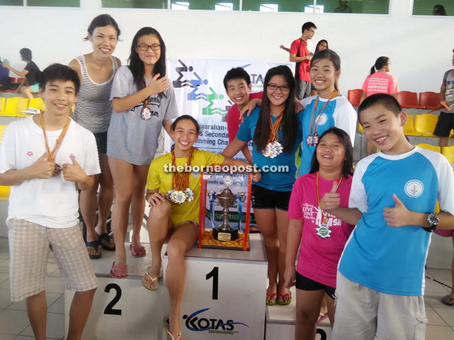 Pamela Lau celebrating the historic achievement with Lodge Secondary School swimming team after scoring their maiden win in the 5th Samarahan-Kuching Divisions Primary and Secondary Schools Swimming Championship yesterday.