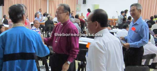 Bolly (third right) greets participants at the forum.