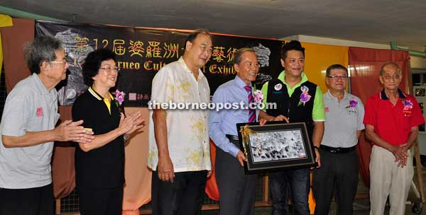 Ong (third right), a representative, presents an art portrait as souvenir to Tiong while others from Sibu Chinese Ink Painting Association, Rejang Chinese Poetry and Calligraphy Association, Photographic Society of Sibu and Sibu Calligraphy Society look on.