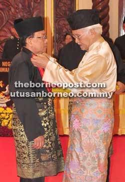 TAHNIAH: Tun Taib menyemat Pingat Pegawai Bintang Sarawak kepada Pemanca Sahari Ghani.