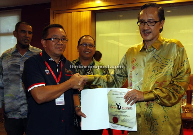 Masidi presenting the 'Raja Kursus' award to Duanis during the closing ceremony of the course yesterday.