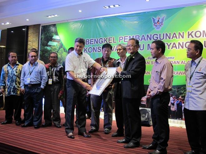 SFD director Supian Ahmad (third right) presents a copy of `Ensera Mayas Enggau Bansa Iban' to Sudarsono. WCS Malaysia director Dr Melvin Gumal is at fourth right.