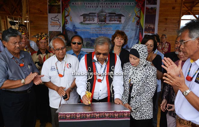 Adenan, flanked by Jamilah and Jabu, signing the plaque to officially recognise Bario as a sub-district after launching the annual Nukunen Festival. — Penerangan Photo.