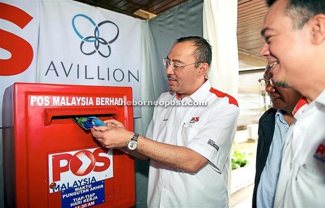 Jailani Johari posting a postcard at the Layang-Layang post office.