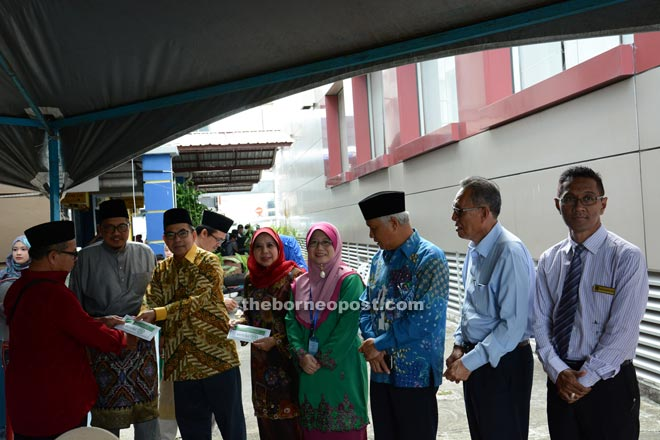Ahmad Lai (third left)presenting the assistance to one of the recipients as Rosey (fourth left), Abang Mohd Shebli (second left) and others look on.