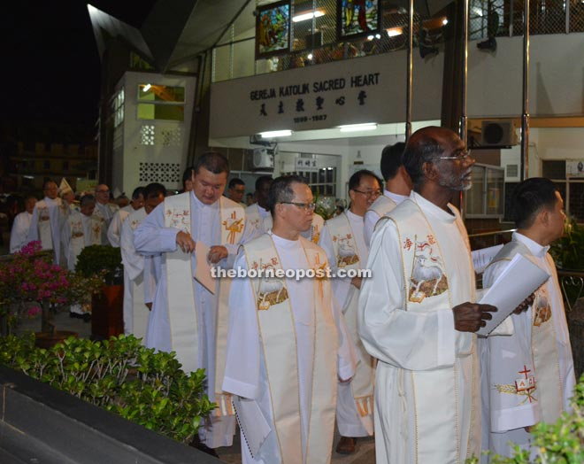 Ministers, priests and bishops in the procession led by the cross-bearers.