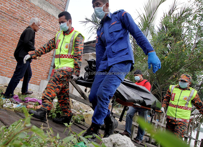 Fire and Rescue personnel bringing in the body of a victim of the capsized boat at Hutan Melintang jetty.— Bernama photo