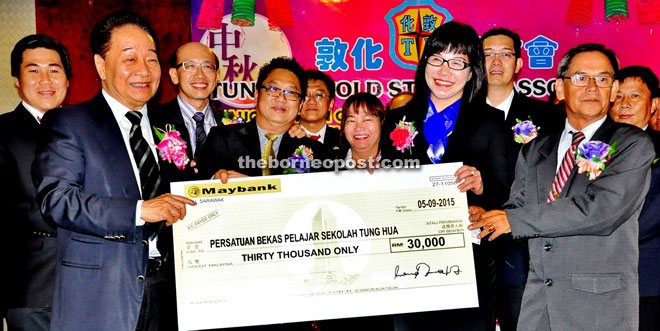 Soon Koh hands over the mock cheque for the old students association to Teresa.
