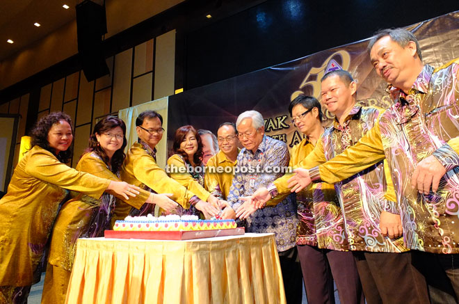 Manyin (fourth right), Jisin (fifth right) and STU members cut the 50th anniversary cake.