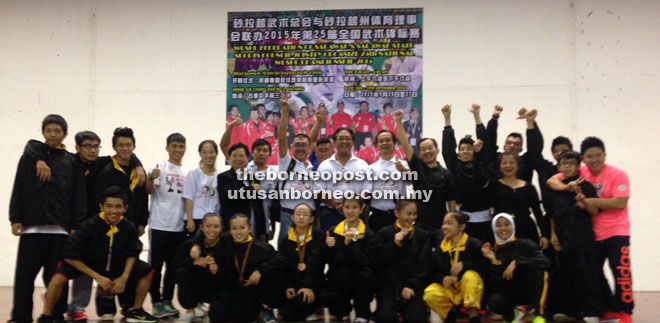 The Sarawak team celebrating with Wushu Federation of Sarawak deputy president-cum-organising chairman James Ting (ninth right) at the end of the competition at SJK Chung Hua No. 3 Alumni Hall yesterday.