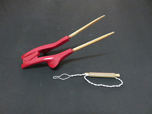 Simple tools like this pair of chopsticks and button hook can make doing tasks easier for disabled people.