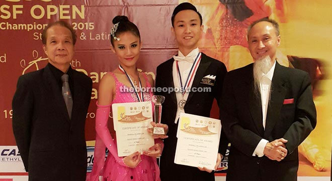 Alexis (second left) and Randell (third left) hold their medals, trophy and certificates in picture taken with Malaysia DanceSport Federation Sports director John Chong (left) and Chester.