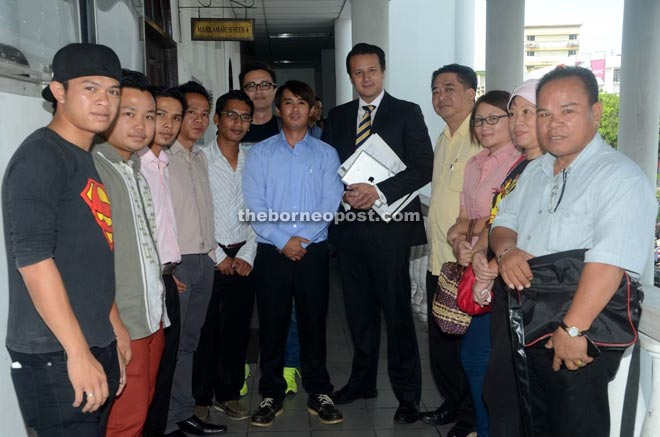 The Sabah Sarawak Keluar Malaysia  movement volunteers with their counsel Tengku Ahmad Fuad outside the Sessions Court after the proceedings yesterday.