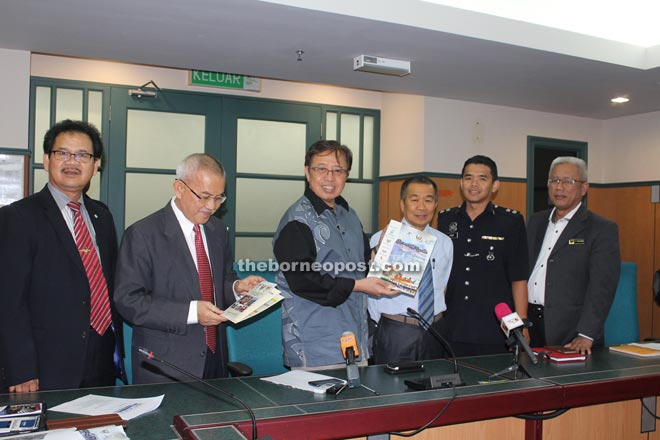 Abang Johari (third left) shows a poster of the Sarawak Regatta while (from left) Ik Pahon, Talib, Naroden (third right) and Hardy (second right) look on.