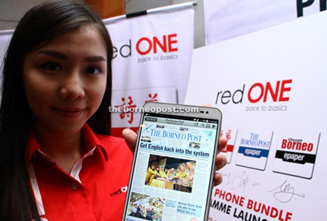 A RedONE staff member shows The Borneo Post's e-paper on a tablet computer.