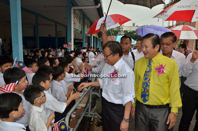 Abang Johari (left) greeting students of SJK Chung Hua No. 4 during his working visit to see the condition of the school yesterday. Accompanying him is Wong (right).