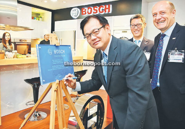 Phang (left) signsa commemorative plaque while  Bosch Southeast Asia president Martin Hayes and Song watch on.