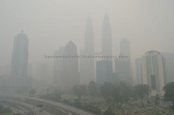 Haze envelops the Petronas Twin Towers as well as other high-rise buildings in Kuala Lumpur. — Bernama photo