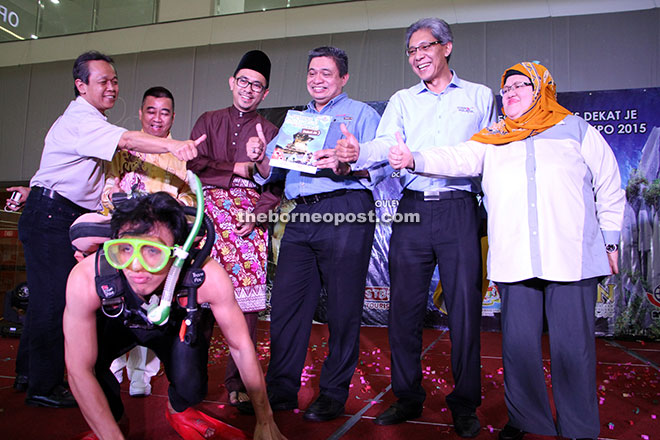 DIVING FORWARD: Tourism Malaysia Domestic Promotion director Iskandar Mirza Mohd Yusof receives the 'Experience Sarawak Best Packages Dekat Je' booklet from a man wearing diving equipment at the launch of the campaign at Boulevard Shopping Mall in Kuching yesterday. The agency hopes to boost domestic tourism with the campaign together with the Sarawak Tourism Board. Also seen are STB Marketing director Benedict Jimbau (far left), Tourism Malaysia director Salahuddin Mohd Arrifin (second right) and Tourism Malaysia Corporate Communication director Azizah Aziz.