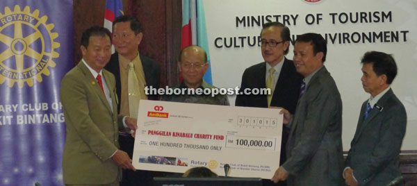 Masidi (third right) and Azman (third left) witnessing the handing over of mock cheque amounting RM100,000 by Bukit Bintang Rotary Club represented by Yap Fatt Lam (left) to Jamili (second right) .