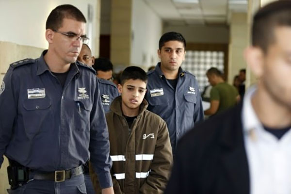 Ahmed Manasra (C), a 13-year old Palestinian accused of taking part in the stabbing of two Israelis earlier this month, is escorted by Israeli security during a hearing at a Jerusalem court on October 30, 2015. - AFP Photo