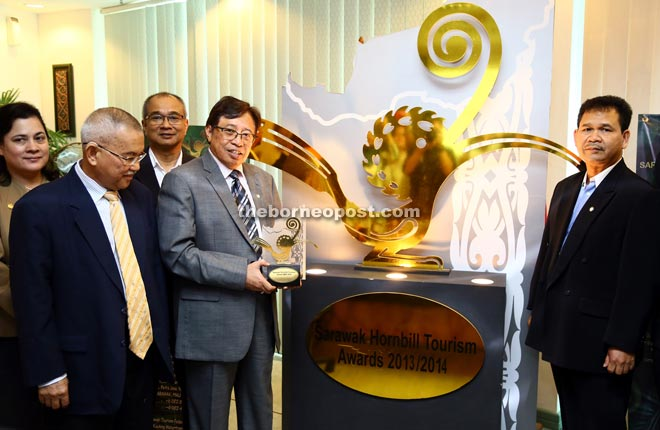 Abang Johari showing a trophy for the Sarawak Hornbill Tourism Awards 2015. Also seen are Talib (second left) and Ik Pahon (right). — Photo by Mohd Rais Sanusi