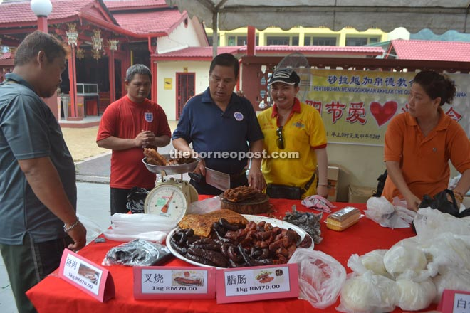 Yii (centre) attends to customers at the roasted pork counter.