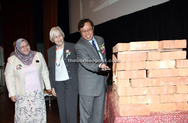 Abang Johari knocks down a brick wall to retrieve a copy of 'Sarawak Historical-Landmarks' in a symbolic gesture to launch the book. Looking on are Heidi and Arpah (left). — Photo by Chimon Upon