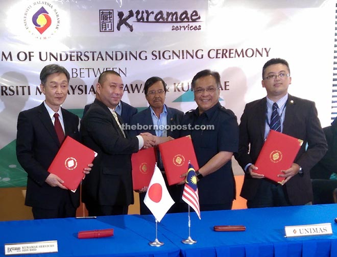 Kadim (second right) exchanging the signed MoU with Kenji, witnessed by Johari (right) and Shinya (left).