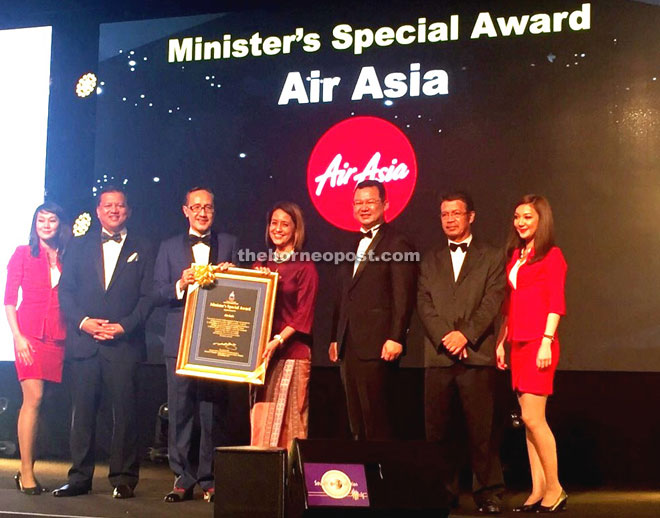 Aireen receiving the 'Best Airline Award' and 'Minister Special Awards' from Masidi during the Sabah Tourism Awards 2015.