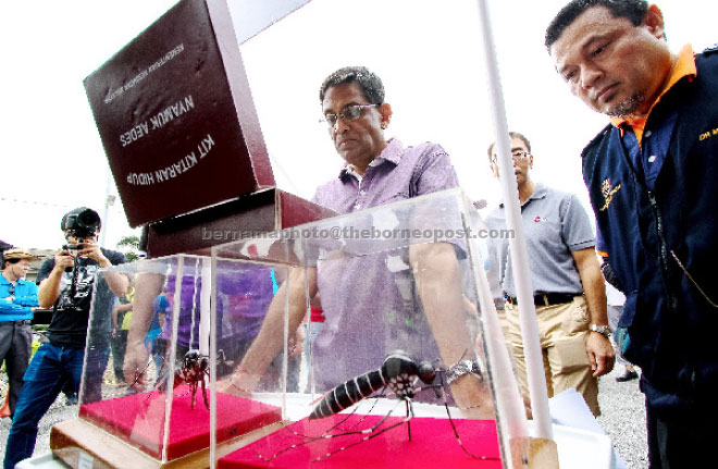 Subramaniam (centre) visit an exhibition booth after launching the clean-up in Kampung Sungai Kayu Ara. — Bernama photo