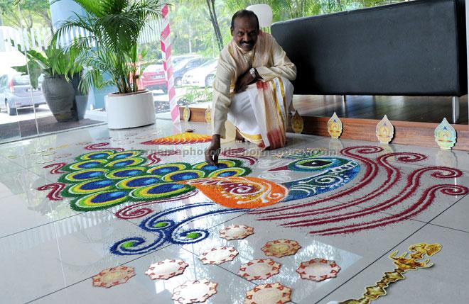 Kandasamy Velayuthan, vice-president of the Malaysian Hindu Sangam, putting the final touches on a 'kolam' at Wisma Bernama. — Bernama photo