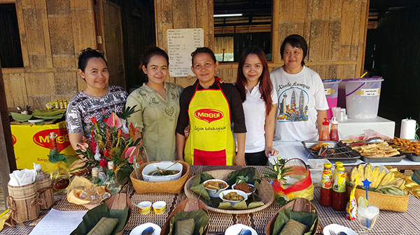 Patis (centre) with her three daughters and a relative (right) and her Bidayuh ethnic offerings. Edelweiss is at left while Estrella is second right.
