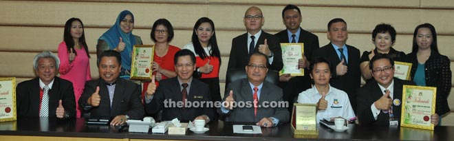 Mayor Datuk Abidin Madingkir (third right) presenting appreciation certificates to the winners of the 1Malaysia National Level Clean Toilets Award 2015 at City Hall yesterday. They are Dr Tan Bee Hwai of Women and Children Hospital Sabah (back row, third left), Carriek Chong of Imago (seated right), Johnson Koh of Oceanus Waterfront Mall (seated left), Shelly Lee Eun Joung of Restoran Deli Korea (standing second right).