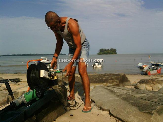 Piruz uses his tools to fix his fishing equipment by his seaside home at Kampung Pasir Pandak.
