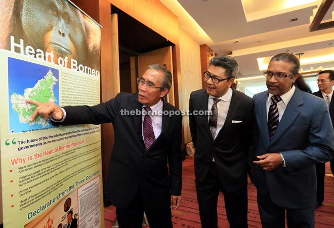 Len (left) pointing on a spot in the HoB map while Sudarsono (second left) and WWF-Malaysia chief executive officer Datuk Dr Dino Sharma look on.