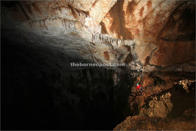 A caver at the edge of the 100-metre sheer drop.