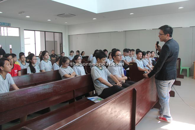 Students listening attentively to a talk by a representative from the Malaysian Institute of Accountants in the school chapel.