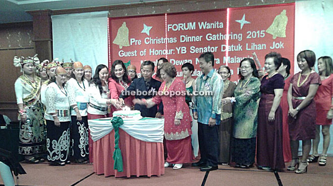 (From sixth left) Lihan and Kijan with other invited guests cutting a Christmas cake during the dinner last Friday.