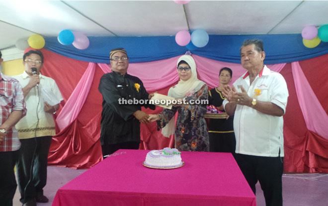 Kampung Klid JKKK chairman Kujang Chalang (left) accepts the RM5,000 allocation from Fatimah.