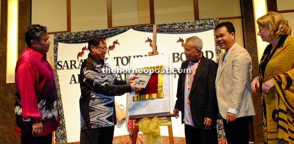 Abang Johari (second left) taking the book out from the case for a closer view after the launching. Also seen from left are Morshidi, Talib, Ik Pahon and Regina.